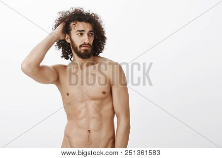 Studio Shot Of Confident Attractive Hispanic Model With Masculine Fit Body, Touching Hair And Lookin
