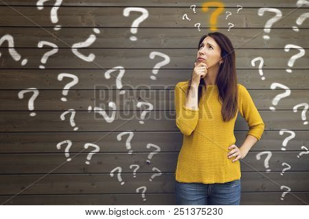 Question Marks With Young Woman In A Thoughtful Pose