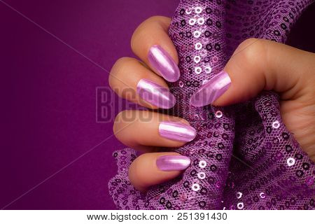 Female Hand With Shiny Purple Nails Is Holding Purple Glittered Fabric On Purple Background, Nail Ca