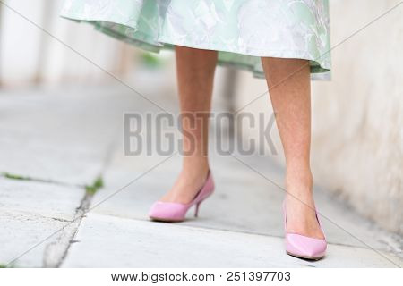 Woman Wearing Stylish Pink High-heeled Formal Court Shoes And A Green Dress Standing Against An Exte