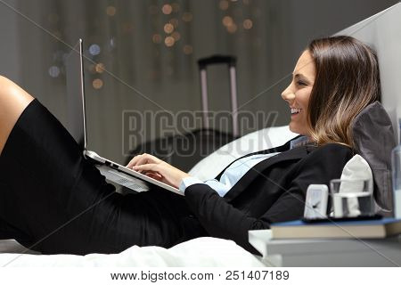 Happy Worker Working With A Laptop In An Hotel Room In The Night