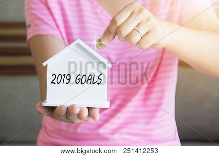 2019 Goals With Women Hand Putting Money Coin In Piggy Bank, Saving Money Concept, Concept Of Financ