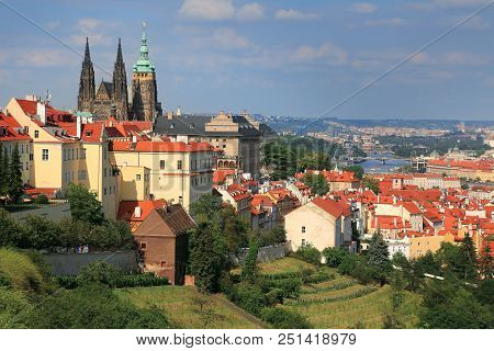 Panaramic View Of St. Vitus Cathedral And Scenic Red Roofs With Background Of Vltava River In Prague