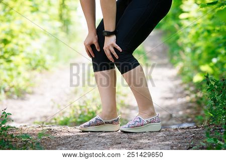 Pain in woman's knee, massage of female leg, injury while running, trauma during workout, outdoors concept poster
