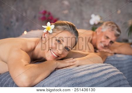 Senior man and beautiful woman lying down on massage beds at spa. Mature couple lying on massage table and smiling while looking at camera. Happy married couple relaxing at wellness spa resort.