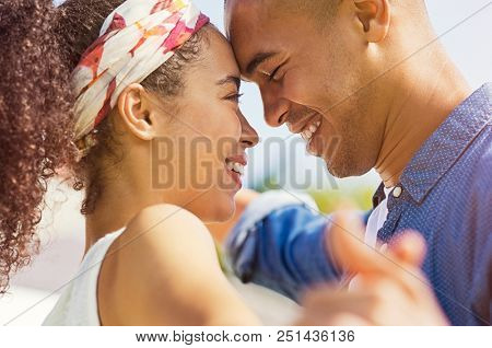 Portrait of happy young couple face to face and looking at each other. Beautiful black couple hugging and smiling at park. African american girl in love embracing her boyfriend in summer.