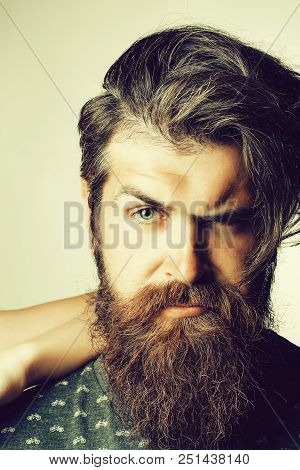 Young Man Hipster With Fashion Beard On Serious Handsome Scowl Face With Squinty Eye And Dark Hair P