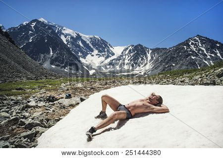 Naked Man On Ice Mountain Against Sky. Young Guy Lying On Snow In Mountains, Sunbathing Enjoying Res