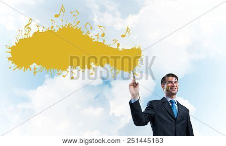 Young and successful businessman in black suit holding paintbrush in hand and smiling while standing with yellow liquid splash with against cloudy skyscape view on background. poster