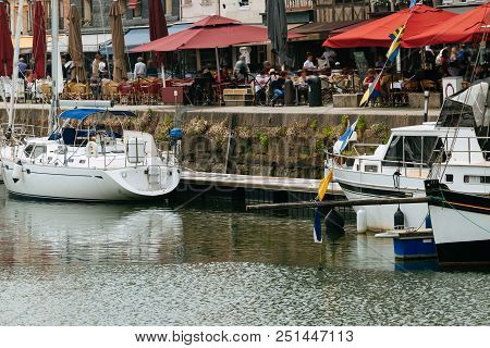Luxury Yachts Moored In Honfleur Marina And Quay With Restaurants. Boats Reflected In The Water Of C
