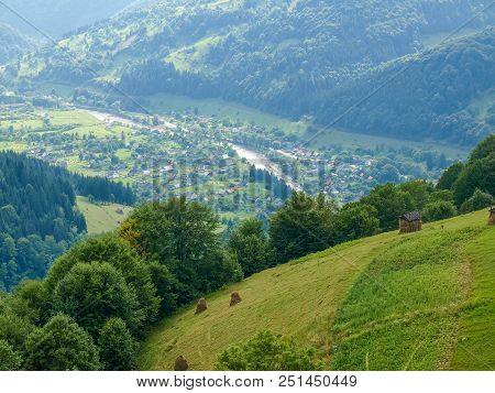 View Of The Mountain Village In Valley From A Mountain Slope With A Hayfields And Forest On The Fore