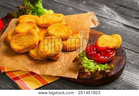 Heap Fried Nuggets From Chicken Poultry Meat On Paper, Ketchup For Nuggets, Lettuce Leaves. Vintage
