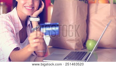 Smiling woman online shopping using tablet and credit card in kitchen . Smiling woman
