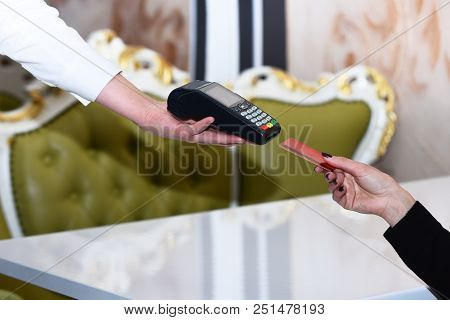 Electronic Finance And Shopping Concept. Credit Card Terminal For Cashless Payments. Cashiers Hand H