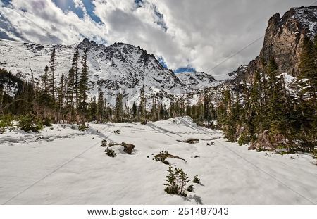 Snowy landscape with rocks and mountains at autumn with cloudy sky. Rocky Mountain National Park in Colorado, USA.