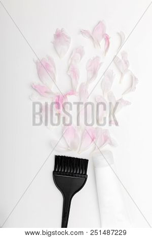 brush for dyeing hair, a tube with hair dye and flower petals. top view poster
