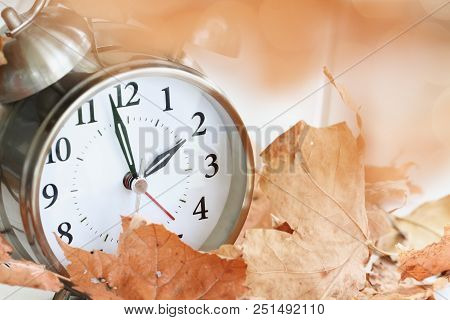 Alarm Clock In Fallen Autumn Leaves With Shallow Depth Of Field. Daylight Savings Time Concept With