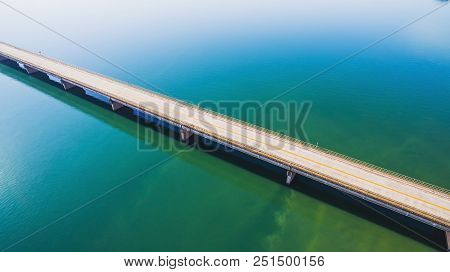 Aerial View Of A Long Highway Bridge Above A River.