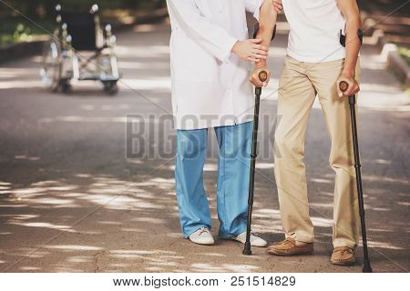 Doctor Helping Old Man Patient With Crutches. Care For Elderly People Concept. Concepts Of Health Ca