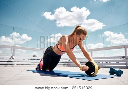 Slim lady is training abdominal muscles with wheel. She is looking at outfit while doing effort on open terrace. Workout for being healthy concept poster