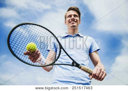 Young Guy In Shirt Ready To Serve On Tennis Court.recreation Concept. Sport Concept. Bottom View. At