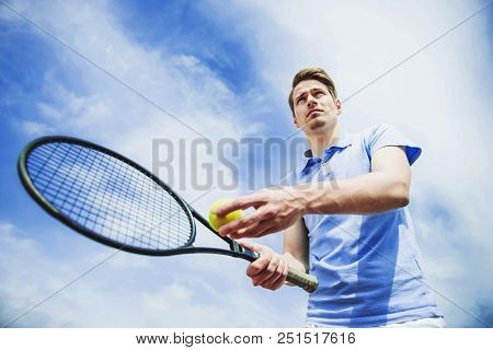 Young Guy In Shirt Ready To Serve On Tennis Court. Recreation Concept. Sport Concept. Bottom View. A