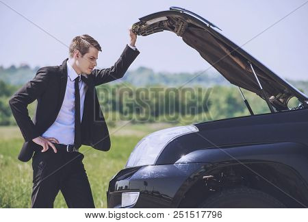 Worried Young Businessman Examining Broken Car Engine At Countryside.road Accident. Man Businessman