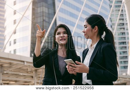 Business Woman Holding Mobile Phone And Talking With Partner While Standing In Modern City, Professi