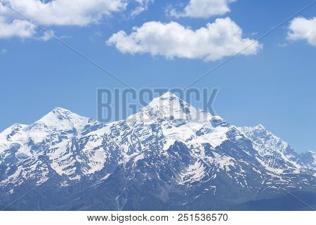Snowy Mountain Peak Against A Blue Sky With White Clouds. Mountain Landscape Of The Rocky Mountain