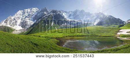 Mountain Landscape Of Svaneti On Bright Summer Sunny Day. Mountain Lake, Hills Covered Green Grass O