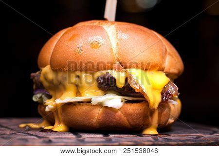 Burger with melted cheese for football fans. Big cheeseburger with melted cheese