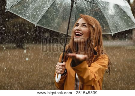 Waist Up Portrait Of Smiling Pretty Female Enjoying Rainy Weather. She Is Standing Under Umbrella An