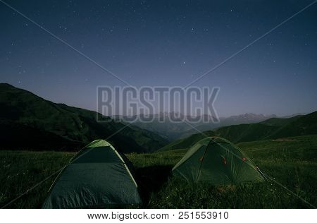 Night Landscape Of Two Camping Tents And A Mountain Range At The Background. Chaukhi Mountain Range