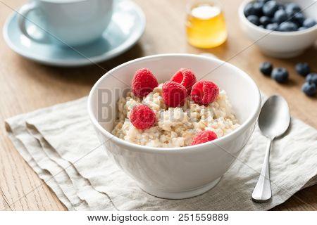 Healthy Breakfast Oatmeal Porridge Bowl With Berries Honey. Cup Of Green Tea On Background. Nutritio