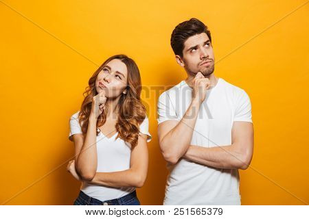 Image of happy young people man and woman in basic clothing thinking and touching chin while looking aside isolated over yellow background