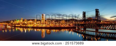 City Of Downtown Portland Oregon Skyline Along Willamette River By Steel Bridge During Evening Blue