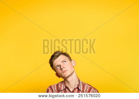 Pensive Thoughtful Contemplative Brooding Man Looking Up. Portrait Of A Young Guy On Yellow Backgrou