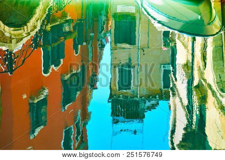 Venetian mirror - Buildings, small bridge, boat and blue sky reflect in the water surface of canal. Venice in water reflections