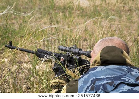 Hunting Season. A 35-40-year-old Man Hunts And Targets A Firearm In The Grass.