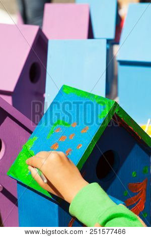Child Hand Painting A Birdhouse Bright Colors Of Blue And Purple. Kids Woodcraft Lesson, Making Wood