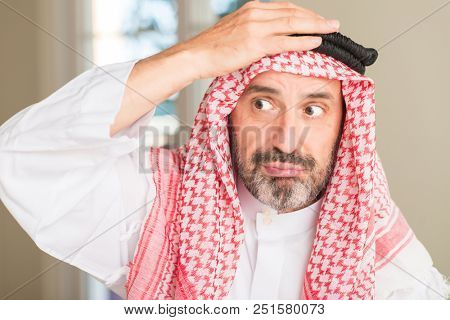 Middle age arabian man at home stressed with hand on head, shocked with shame and surprise face, angry and frustrated. Fear and upset for mistake.