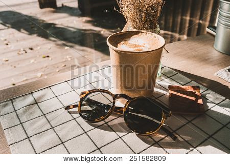 Cappuccino In Take Away Coffee Cup And Sunglasses On Table Cloth With Dry Flower On Wood Table With