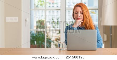 Redhead woman using computer laptop at home serious face thinking about question, very confused idea