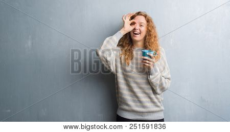 Young redhead woman over grey grunge wall drinking a cup of coffee with happy face smiling doing ok sign with hand on eye looking through fingers