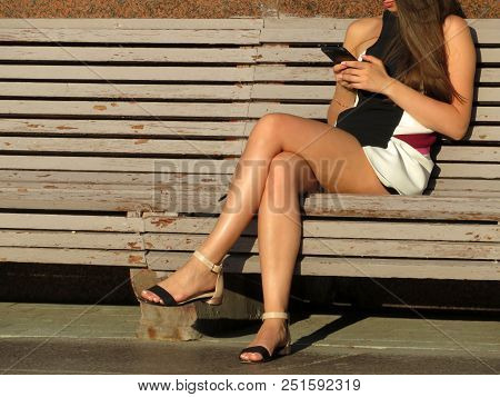 Woman In A Short Dress Sitting With A Smartphone In Her Hand On The Wooden Bench. Girl With Long Bro