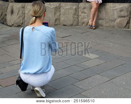 Young Woman Takes Pictures Of A Girl In Short Dress On A Smartphone Camera. Photo Shoot In A Summer