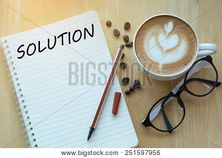 Solution Word On Notebook With Glasses, Pencil And Coffee Cup On Wooden Table. Solution Concept.