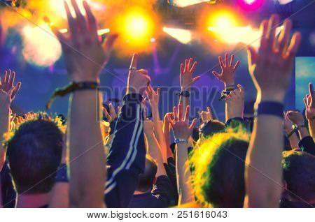 concert crowd in front of colorful stage lights
