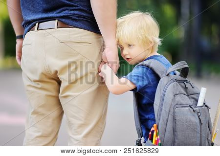 Back to school concept. Little pupil with his father. First day of primary school. Education for small kids. poster