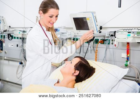 woman physician in intensive medical care department of hospital checking data of patient